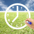 Hand is drawing a clock on lawns and blue sky. — Stock Photo
