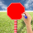 Hand and red sign on the lawn and blue sky. — Stock Photo