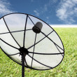 Satellite dish on the grass and blue sky. — Stock Photo