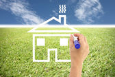 Hands are painted house on grass and blue sky. — Stock Photo