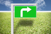 Green signs with arrows on the grass and blue sky. — Stock Photo
