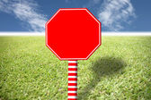 Red sign on the lawn and blue sky. — Stock Photo