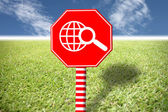 Red labels with images world on grass and blue sky. — Stock Photo