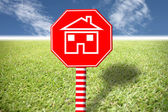 Red labels with home picture on grass and blue sky. — Stock Photo
