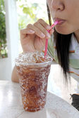 Woman sucking cola in glass. — Stock Photo