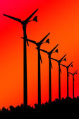 Silhouette Wind turbines on Red background. — Stock Photo