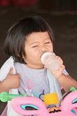 Asian baby child girl are Sucking Baby Bottle. — Stock Photo