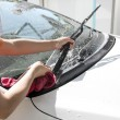 Stock Photo: White car washing Windshield wiper with Water hose.