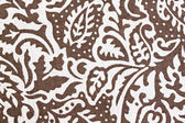 White patterned leaves on brown fabric. — Stockfoto
