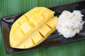 Ripe mango and sticky rice in dish on banana leaves. — Stock Photo