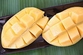 Ripe mango with slices in black dish on banana leaves. — Stock Photo