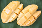 Ripe mango with slices on banana leaves. — Stock Photo