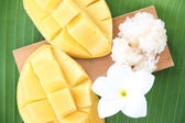 Ripe mango and sticky rice in bamboo dish on banana leaves. — Stock Photo