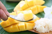 Ripe mango and sticky rice in spoon on banana leaves. — Stock Photo