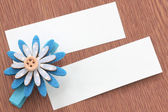 Blue artificial flowers and note paper stuck on dark wood. — Stock Photo