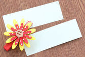 Red artificial flowers and note paper stuck on dark wood. — Stock Photo