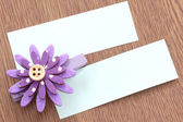 Purple artificial flowers and note paper stuck on dark wood. — Foto de Stock