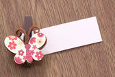 Brown artificial butterfly and note paper stuck on dark wood. — Stockfoto
