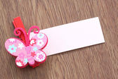 Pink artificial butterfly and note paper stuck on dark wood. — Foto de Stock