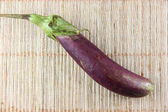 Purple eggplant on bamboo pattern background. — Stock Photo