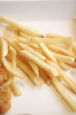 French fries and fried chicken on dish. — Stock Photo