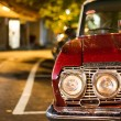 Red retro car, standing in the rain on a street — Stock Photo