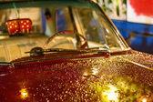 Voiture rétro rouge, debout sous la pluie sur une rue — Photo