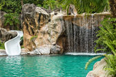 Swimming pool with waterfall and slide at high resolution — Stock Photo