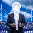 Man with a light bulb head in front of solar panels and wind turbines — Stock Photo