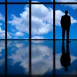 Business Man Looking Out of High Rise Office Window at Blue Sky and Clouds — Stock Photo #22849402