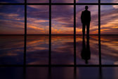 Homme d'affaires regarde par la fenêtre de bureau grande hauteur au coucher du soleil — Photo