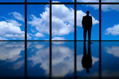 Business Man Looking Out of High Rise Office Window at Blue Sky and Clouds — Stockfoto