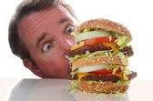 Double deck hamburger and man with eyes wide open — Stock Photo