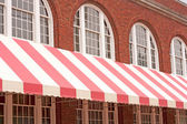 Brick Building With Striped Awning — Stock Photo