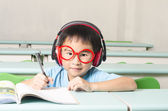 Smart student writing and wearing headphone — Stock Photo