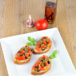Bruschetta on wooden table and white plate from the top — Stock Photo