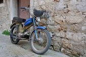 Old motorcycle standing at a wall — Stok fotoğraf
