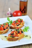 Bruschetta with oil on wooden table and white plate — Stock Photo