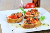 Bruschetta with oil on wooden table and white plate from the sid — Stock Photo