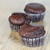 Sweet chocolate muffins on wooden table — Stockfoto