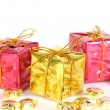 Gifts on white background with golden stars in the front — Stock Photo