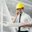 Engineer with blue prints and cell phone — Stock Photo