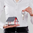 Woman holding a model of a detached house and the keys  — Stock Photo