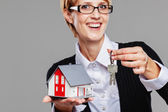 Attractive female real estate agent presenting a detached house model and keys — Stock Photo