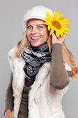 Woman in fall fashion holding a sunflower to her head and smiling — Stock Photo