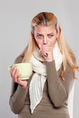 Ill woman holding a mug of tea and coughs — Stock Photo