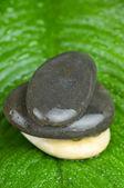 Stapel stenen op het groene blaadje met water drops — Stockfoto
