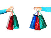 Two hands holding gift bags isolated on white — Stock Photo