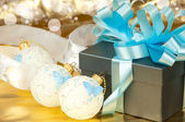 Gift boxes with blue ribbon and christmas toys on golden background — Stock Photo