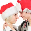 Happy couple in santa's hats isolated on white background — Stock Photo